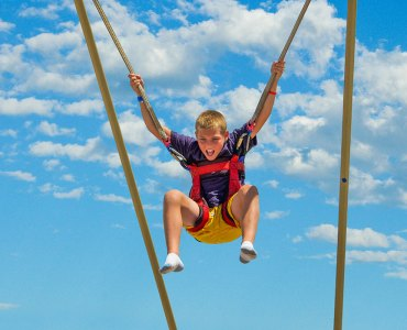 Image of boy jumping in the air on the Extreme Air Jump in the Boathouse District