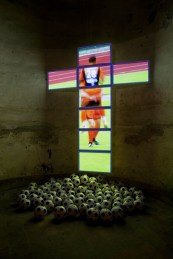 Orlan, No comment, 2008. Video installation, video projection on a screen in the shape of a cross and 100 printed footballs, variable dimensions.