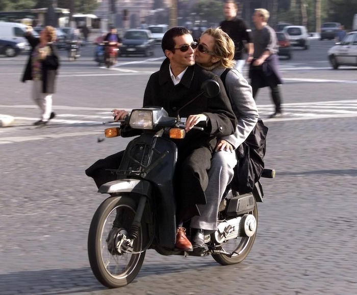 A Roman couples rides a moped without helmet in th