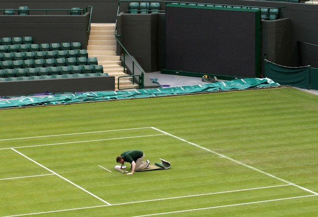 LONDON, ENGLAND - JUNE 22: A worker checks the grass on Day Three of the Wimbledon Lawn Tennis Championships at the All England Lawn Tennis and Croquet Club on June 22, 2011 in London, England. (Photo by Oli Scarff/Getty Images)