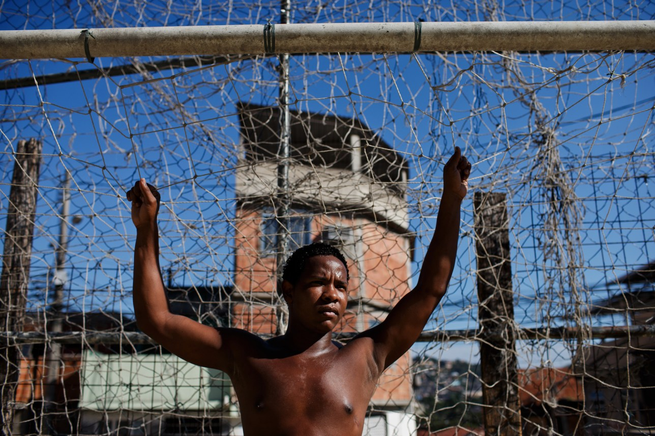 RIO DE JANEIRO, BRAZIL - JUNE 29: Twenty-eight year old Wagner from the Complexo do Alemao favela waits for the ball while standing on goal during a game of football at the Complexo do Alemao favela on June 29, 2013 in Rio de Janeiro, Brazil. It was at the end of 2010 that under the stage of pacification some 300 police officers went into the Complexo do Alemao with tanks and helicopters to drive out the criminal gangs to establish a permanent police presences and to set up social services such as schools, healthcare centers, and rubbish collection. The Complexo do Alemao favela is, with a population of 100, 000 and stretching for more than 3 kilometers with a maze of narrow alleys and stairways, one of the largest favelas in Rio de Janeiro. (Photo by Jasper Juinen/Getty Images)