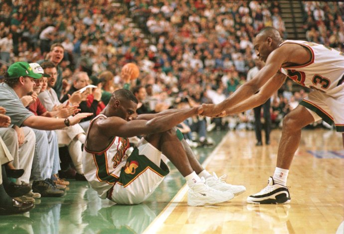 18 May 1996: Hersey Hawkins #33 of the Seattle Supersonics helps teammate Shawn Kemp #40 to his feet as fans cheer them on during the Sonic''s 102-72 game one victory over the Utah Jazz in the NBA Western Conference Finals at Key Arena in Seattle, Washing