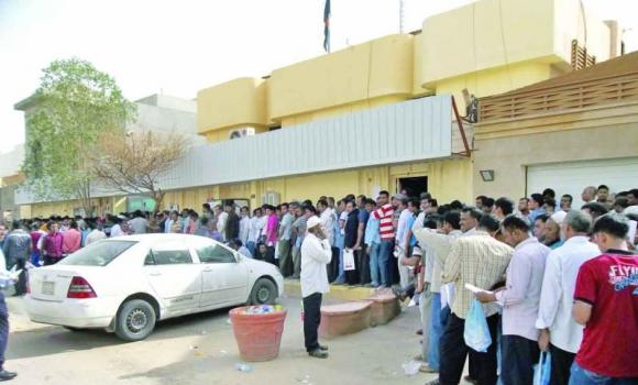 Bangladeshis stand in line for consular services at their embassy in Riyadh on Sunday. (AN photo)