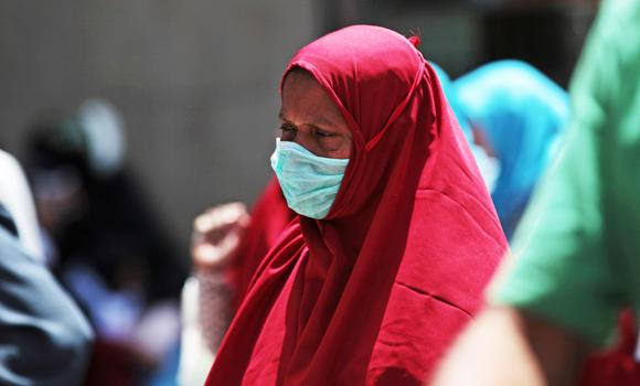 In this photo taken May 13, 2014, a Muslim pilgrim wears a surgical mask to prevent infection from MERS coronavirus in the holy city of Makkah. The global death toll from MERS has surpassed the 200-mark, including 177 in Saudi Arabia.