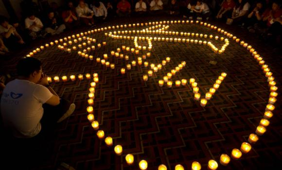 In this April 8, 2014 file photo, relatives of Chinese passengers onboard Malaysia Airlines Flight 370 offer prayers during a candlelight vigil for their loved ones at a hotel in Beijing, China. (AP Photo)