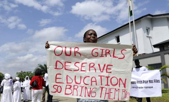 A woman holds a sign to call for the release of more than 200 schoolgirls kidnapped by Boko Haram militants on May 19, 2014 during a sit-in organized by Human Rights organisations in Abidjan. (AFP Photo/ Sia Kambou)