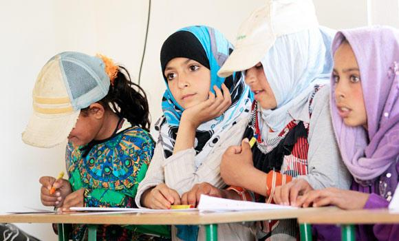 Syrian girls attend a class at a refugee camp school. (Reuters)