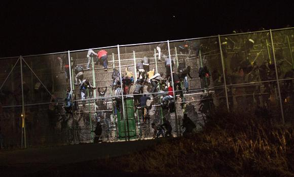 Sub-Saharan migrants scale a metallic fence that divides Morocco and the Spanish enclave of Melilla, early in the morning on Wednesday. (AP Photo/Santi Palacios)