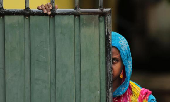 A woman looks out on the street, in Aluthgama, a town 50 km south of Colombo, Sri Lanka.