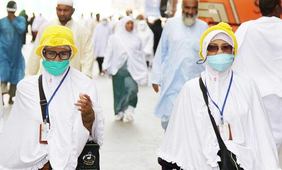 Asian Muslim pilgrims wear nose and mouth masks on their way to Islam's holiest shrine, the Kaaba, in the Grand Mosque in the Saudi city of Mecca in Saudi Arabia, in this May 27, 2014 photo.