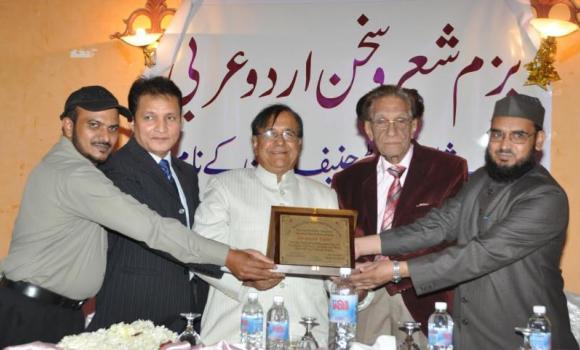 Dr. Haneef Tarin receives a memento from Pakistani poet Mashkoor Hussain Yaad and Bazm-e-Sher O Sukhan President Arif Muzaffarnagri in Riyadh.