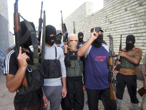 Masked Sunni gunmen pose for a photo during a patrol outside the city of Falluja April 28, 2014.