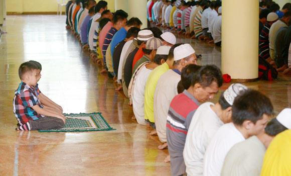 Filipino Muslim children (L) pray with other worshippers at the Golden Mosque in Manila on Saturday on the eve of Ramadan.