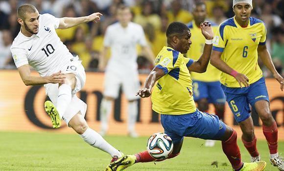 France's Karim Benzema shoots as Ecuador's Frickson Erazo attempts a block.