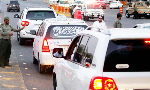Saudi policemen check permits in a car on the road to Mecca.