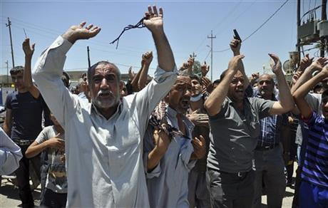 In this June 23, 2014, photo, mourners chant slogans against the al-Qaida breakaway group Islamic State of Iraq and the Levant after they bury 15 bodies in the village of Taza Khormato near the northern oil-rich city of Kirkuk, Iraq. U.S. teams of special forces going into Iraq after a three-year gap will face an aggressive insurgency, a splintering military and a precarious political situation as they help Iraqi security forces improve their ability to battle Sunni militants.