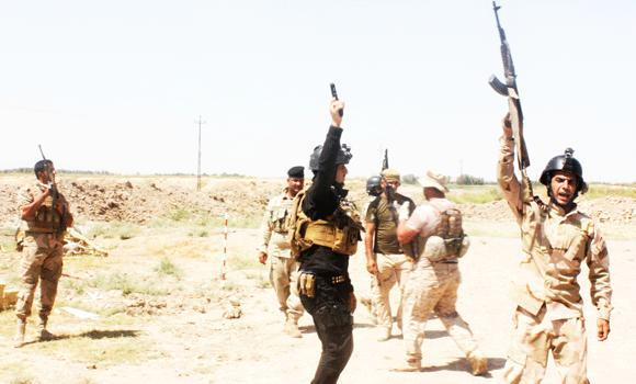 Members of the Iraqi security forces shout slogans as they carry weapons during clashes with militant group Islamic State of Iraq and the Levant (ISIL) in Muqdadiyah in Diyala province on Thursday.