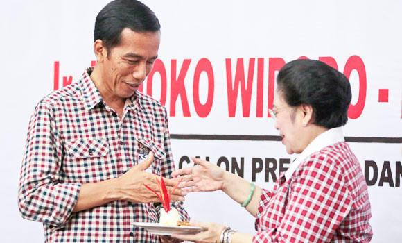 Indonesian presidential candidate Joko Widodo, left, receives a piece of 'tumpeng', a Javanese traditional ceremonial dish of rice, from the chairwoman of Indonesian Democratic Party-Struggle (PDI-P) Megawati Sukarnoputri flash 'V' sign during a ceremony marking the start of his presidential election campaign in Jakarta, Indonesia, on Wednesday. (AP)