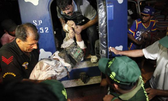 Pakistani police commandos help an injured colleague at Jinnah International Airport where security forces are fighting with gunmen who disguised themselves as police guards and stormed a terminal used for VIPs and cargo. (AP)
