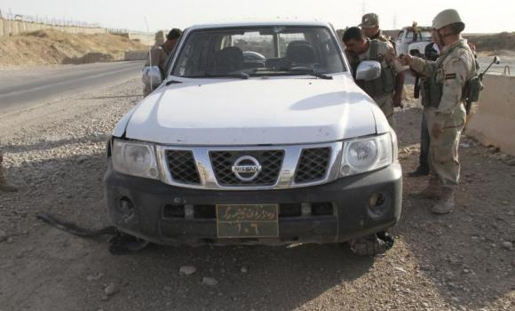 Kurdish security forces look at a damaged vehicle belonging to them during clashes with the Sunni militant group Islamic State of Iraq and the Levant (ISIL) on the outskirts of Diyala on June 14, 2014.