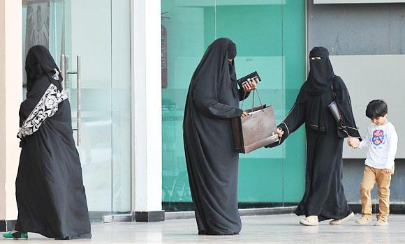 Saudi women stand at the entrance of a shopping mall.