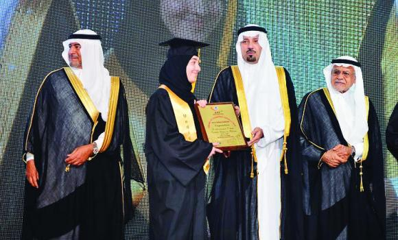 Makkah Gov. Prince Mishaal bin Abdullah, 2nd right, honors one of the graduates while Sobhi Batterjee, chairman of the Board of Trustees, left, looks on.