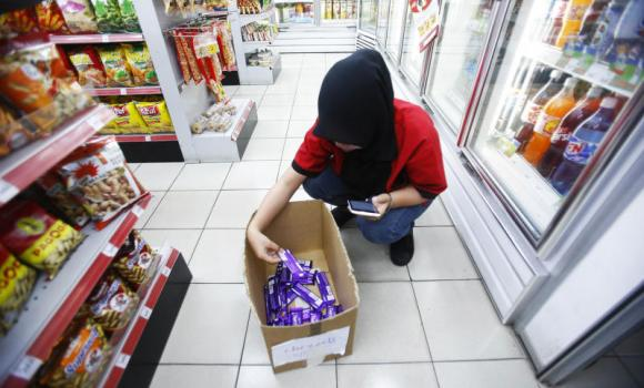An employee removes Cadbury Dairy Milk Hazelnut and Cadbury Dairy Milk Roast Almond products from a shop in Shah Alam, outside Kuala Lumpur, on May 27, 2014 after chocolate maker Cadbury Malaysia recalled them after they tested positive for traces of pork DNA. (Reuters/Samsul Said)