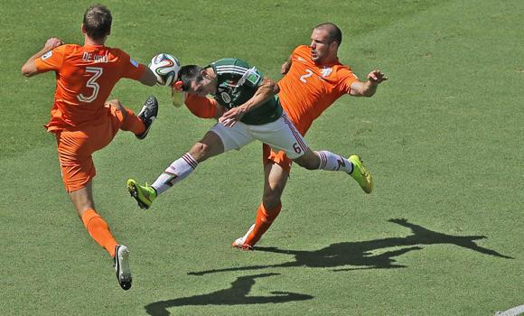 Mexico's Hector Herrera, center, challenges for the ball with Netherlands' Stefan de Vrij, left, and Ron Vlaar during the World Cup round of 16 soccer match between the Netherlands and Mexico at the Arena Castelao in Fortaleza, Brazil, on Sunday.
