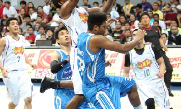 Paul Harris of Talk 'N Text takes the ball to the hoop against San Mig Coffee's Joe Devance of San Mig.