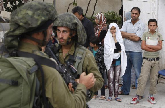 Palestinians stand outside their house as Israeli soldiers take part in an operation to locate three Israeli teens near the West Bank City of Hebron June 21, 2014.