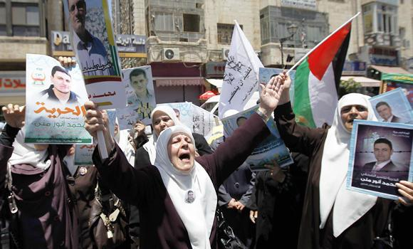 Palestinian women shout slogans and hold portraits of detainees on June 9, 2014 in the West Bank city of Ramallah during in a demonstration in support of 125 Palestinian prisoners detained in Israeli jails.