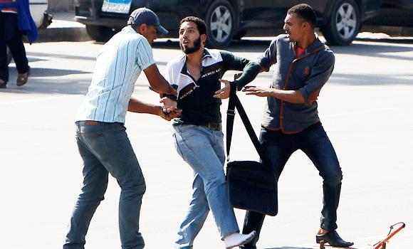 Plain-clothes riot policemen detain a student supporter (C) of the Muslim Brotherhood and ousted President Mohamed Mursi, after clashes broke out during a demonstration outside Cairo University, in thi May 14, 2014 photo.