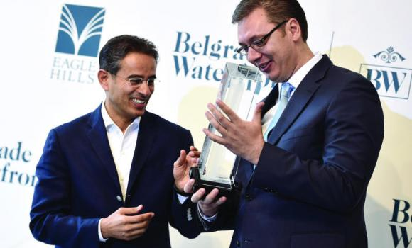 Serbian Prime Minister Aleksandar Vucic receives a gift from Mohammed Alabbar, head of Eagle Hills company, during a presentation in Belgrade.