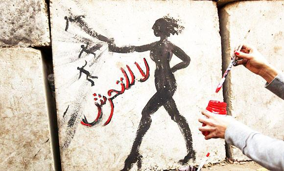 """In this Dec. 14, 2012 file photo, an Egyptian activist drawing graffiti depicting a woman and reading in Arabic: """"No to Sexual Harassement"""" on a wall outside the presidential palace in Cairo."""