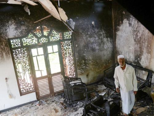 A Sri Lankan resident surveys the damage to a charred Muslim-owned home following clashes between Muslims and an extremist Buddhist group in the town of Alutgama, Sri Lanka, on Tuesday.