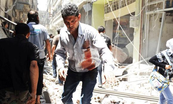 A man with bloodstains on his shirt walks on rubble at a site hit by what activists said was an airstrike by forces loyal to Syria's President Bashar al-Assad at the Damascus suburb of Saqba on Wednesday.