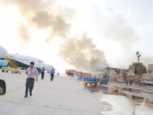 Smoke rises above the Jinnah International Airport where security forces battle militants in Karachi on Monday.