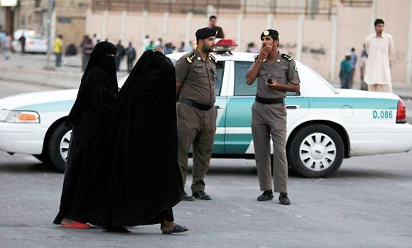 Women walk past members of Saudi security forces as they keep guard in Manfouha, southern Riyadh, in this November 14, 2013 file photo.