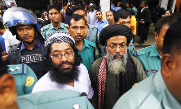 Police escort members of the militant group Harkat-ul Jihad Islami (HUJI) to a prison van after a verdict at the Dhaka Judge Court on Monday.