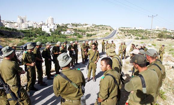 Israeli soldiers receive instructions at the start of a search operation in the village of Halhul, near the West Bank town of Hebron, on Sunday, to try to locate the three teenagers.