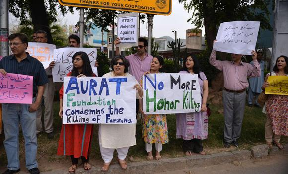 In this file photo taken May 29, 2014, Pakistani human rights activists protest in Islamabad against the killing of a pregnant woman, who was beaten to death with bricks by members of her own family for marrying a man of her own choice in Lahore. Undeterred by the furor caused by that murder, a Pakistani couple in Punjab province on Thursday killed their own 17-year-old daughter and her 31-year-old man after the lovers married without the family's consent.