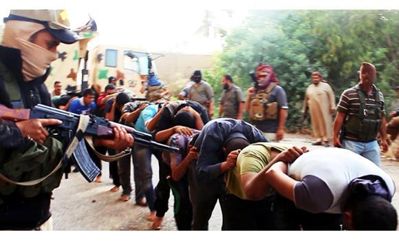 This file image posted on a militant website on June 14, 2014 shows ISIL militants leading away captured Iraqi soldiers dressed in plain clothes after taking over a base in Tikrit, Iraq. On Sunday, ISIL militants crucified eight fighters of a rival rebel group in Aleppo, Syria, the Syrian Observatory for Human Rights said.