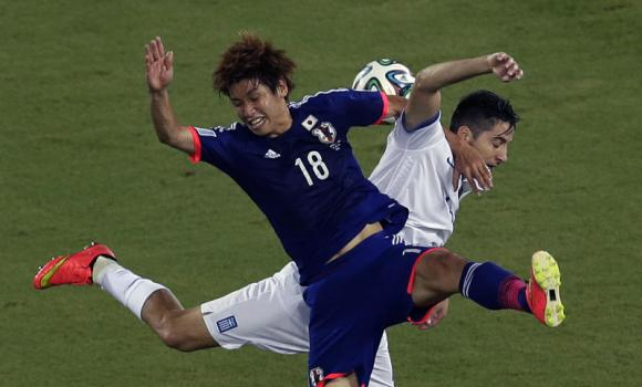 Japan's Yuya Osako, front, and Greece's Kostas Manolas challenge for the ball during the group C World Cup soccer match between Japan and Greece at the Arena das Dunas in Natal, Brazil, Thursday, June 19, 2014.