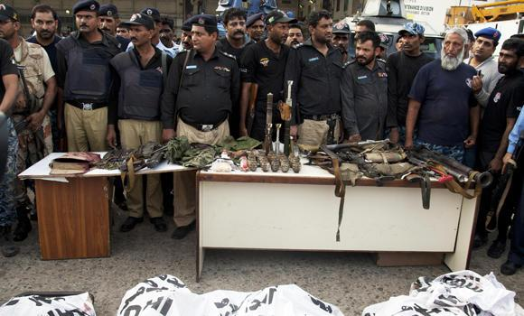 Pakistani police officers display confiscated ammunition and the bodies of terrorists who attacked the Jinnah International Airport in Karachi on Sunday night.