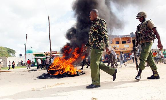 Kenyan police officers walk past a bonfire used to barricade a main road after unidentified gunmen recently attacked the coastal Kenyan town of Mpeketoni, June 17, 2014.
