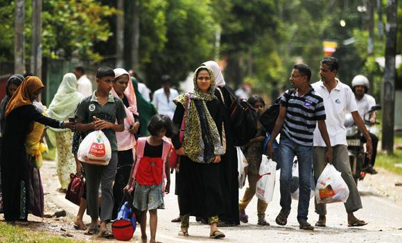 Sri Lankan Muslims walk to safer places following attacks by hard-line Buddhist group Bodu Bala Sena in Aluthgama, 50 kilometers south of Colombo, Sri Lanka, on June 16, 2014.