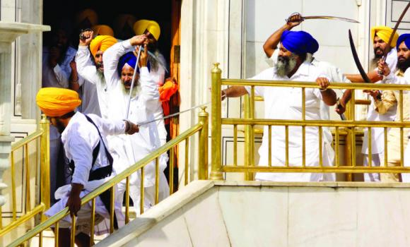 Members of a hard-line Sikh group clash with guards of the Sikh's holiest shrine, the Golden Temple, in Amritsar, India, on Friday. (AP)