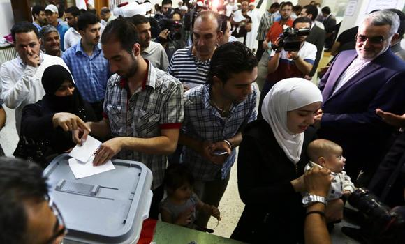 Syrians cast their ballots in the country's presidential election on June 3, 2014 at a polling station in Damascus. (AFP)