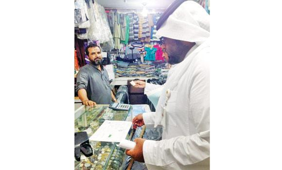 A Labor Ministry inspector in Jeddah checks the shop ownership documents and iqama of an expatriate worker.