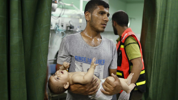 A Palestinian baby boy is carried after being evacuated from a U.N.-run school sheltering Palestinian refugees, which witnesses said was hit by Israeli shelling, at a hospital in the northern Gaza Strip July 24, 2014.